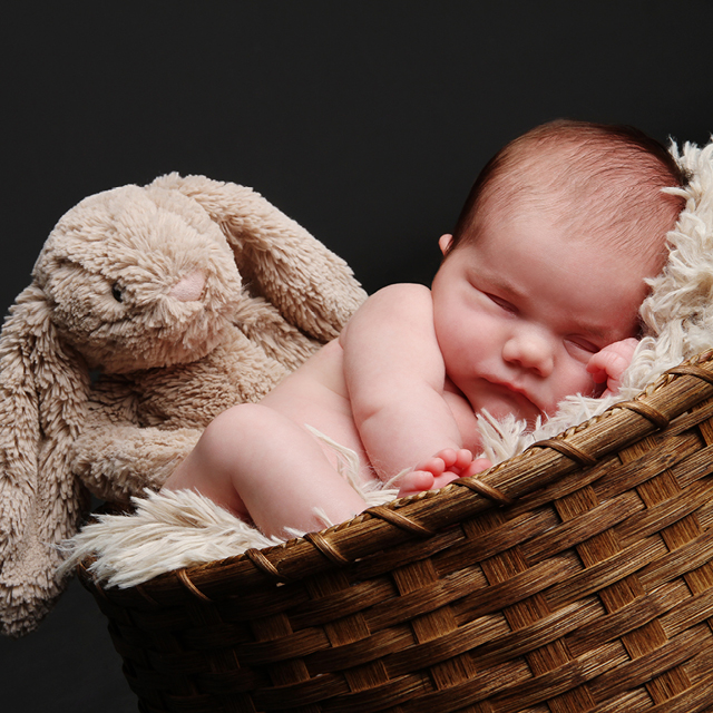 Photo of a newborn lying in a wicker basket with a plush bunny.