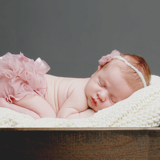 Photo of a newborn wearing a pink tutu and sleeping in a wooden box.