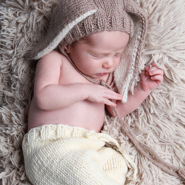 Photo of a newborn wearing bunny ears as an accessory, lying on a cozy blanket.